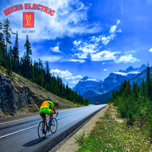A cyclist rides along the road on the Icefields Parkway in Alberta. The photo is branded with a Mikes Electric Banff logo watermark